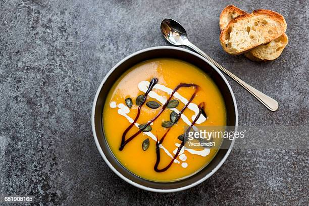 Creamed pumpkin soup in black bowl