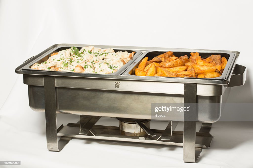 Creamy chicken and baked potatoes in metal pans : Stock Photo