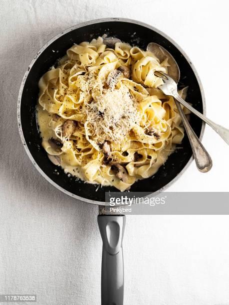 pasta cremosa ai funghi, pasta linguini e funghi, tagliatelle cremose con funghi e parmigiano, - noodle foto e immagini stock