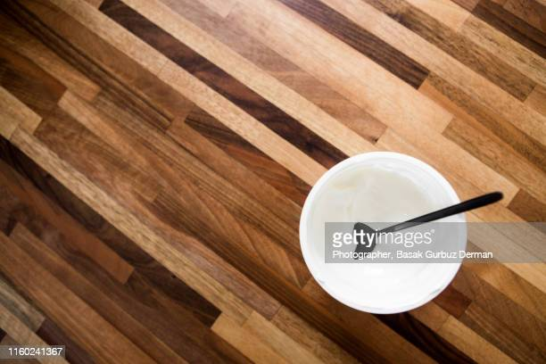 Creamy yogurt and a black spoon on wooden table