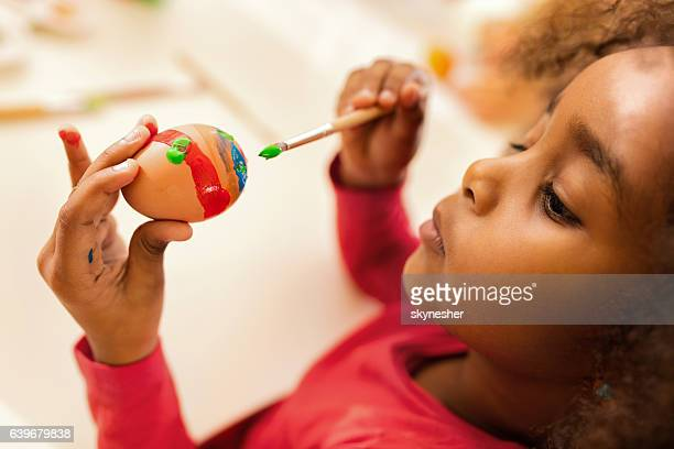 Creative African American little girl painting Easter egg.