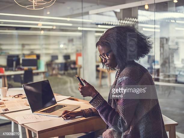 Creative afroamericana mujer mediante teléfono móvil en la oficina