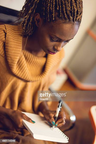 Creative African American woman writing in a notebook.