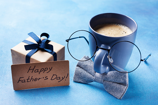 Creative breakfast on Happy Fathers Day with gift box, funny face from cup of coffee, eyeglasses and bowtie. 961506166