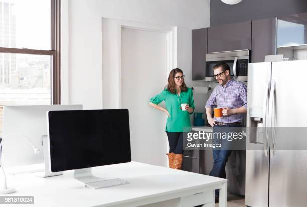 creative business colleagues holding coffee mugs while discussing in office - pause café photos et images de collection