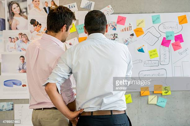 Creative business men looking at a wall chart