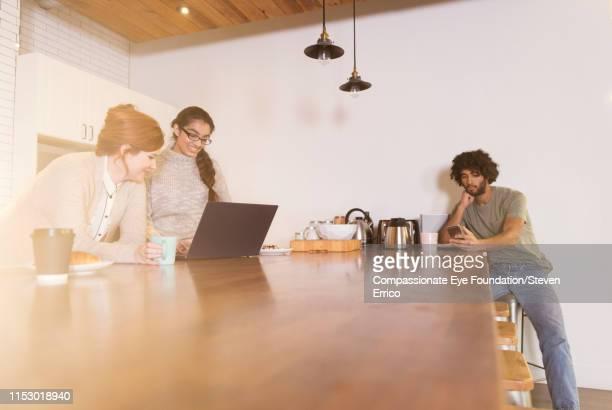 Creative business people having informal meeting in office kitchen