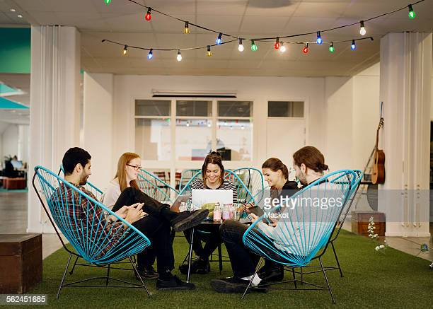 Creative business people using technologies in office canteen