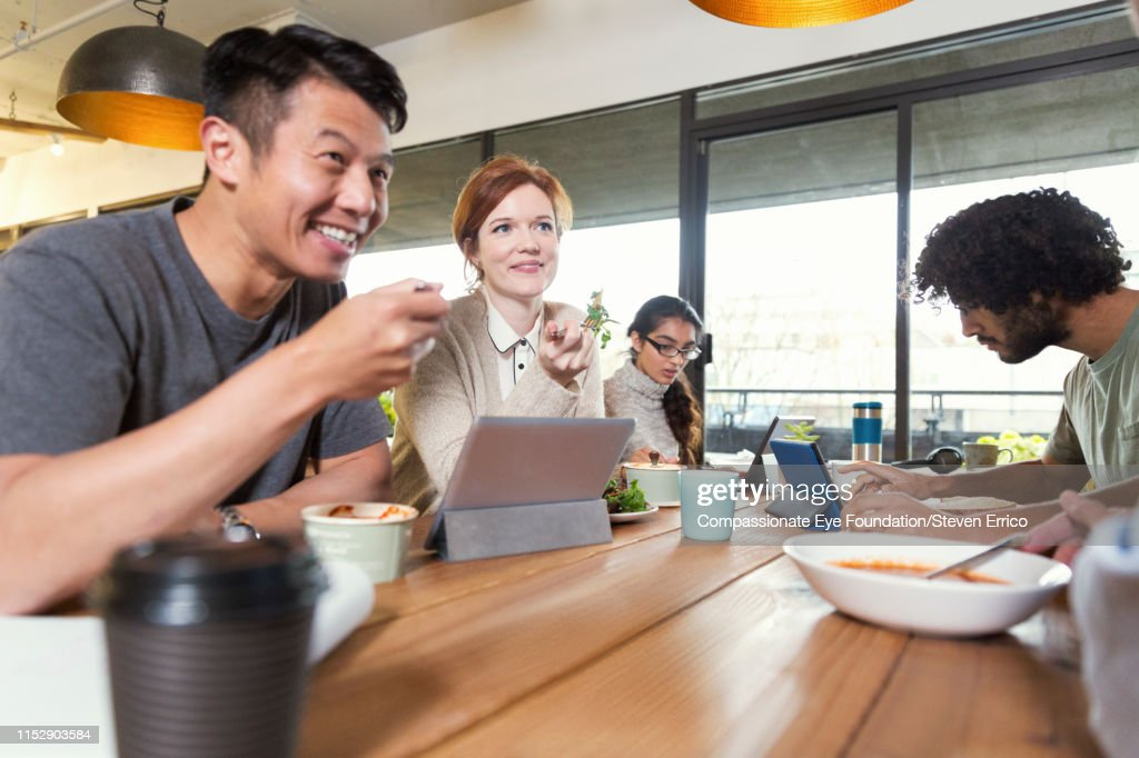 Creative business people working and having lunch in office : Stock Photo