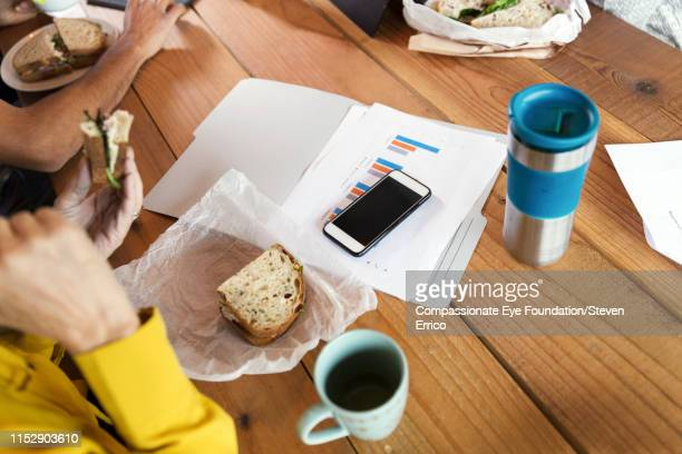 """creative business people working and having lunch in office - """"compassionate eye"""" stock pictures, royalty-free photos & images"""