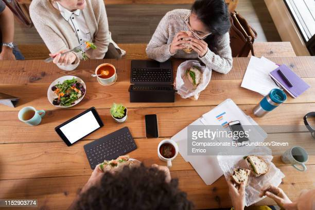 creative business people working and having lunch in office - lunch stock pictures, royalty-free photos & images