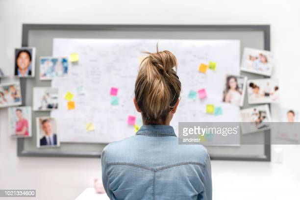creative business woman brainstorming at the office using a whiteboard - business plan stock pictures, royalty-free photos & images