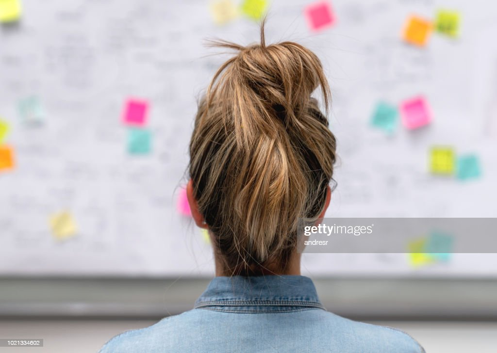 Creative business woman brainstorming at the office using a whiteboard : Stock Photo