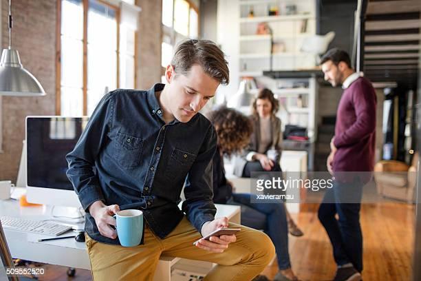 Creativa hombre de negocios verificar teléfono móvil fuera de reunión