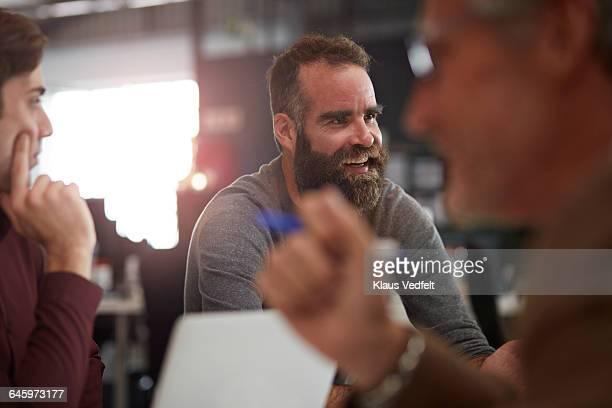 Creative businessman laughing at meeting