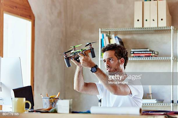 creative businessman making octocopter in office - drone photos et images de collection