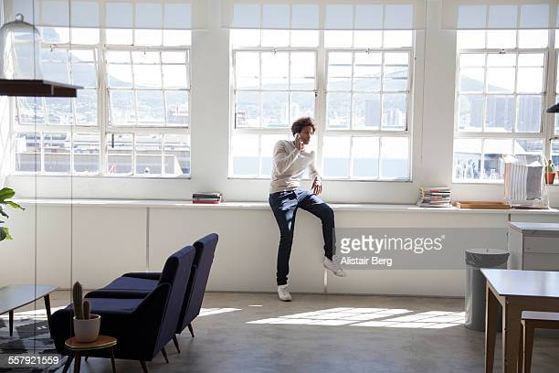 creative businessman talking on phone in office - ジーンズ ストックフォトと画像