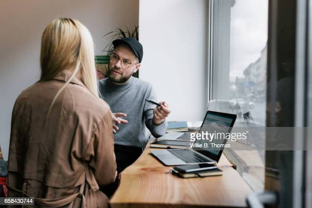 Creative businessman talking with co-worker