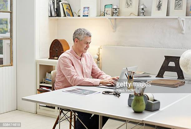 Creative businessman typing on laptop at his desk