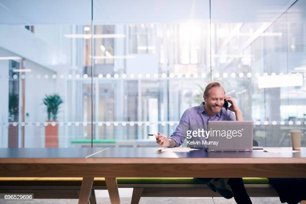 Creative businessman using cell phone in conference room