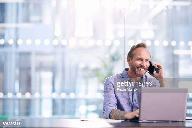 Creative businessman using cell phone in modern office