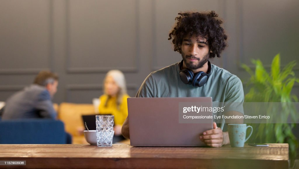 Creative businessman using laptop in co-working space : Stock Photo