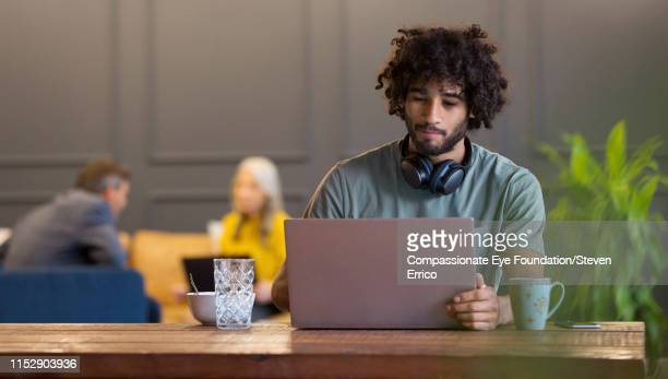 creative businessman using laptop in co-working space - incidental people stock pictures, royalty-free photos & images