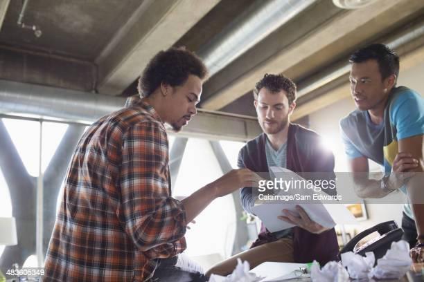 Creative businessmen discussing paperwork in meeting