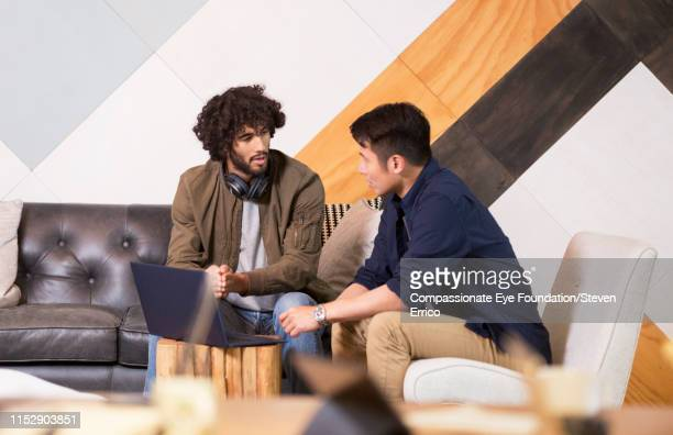 """creative businessmen having informal meeting in co-working space - """"compassionate eye"""" stock pictures, royalty-free photos & images"""