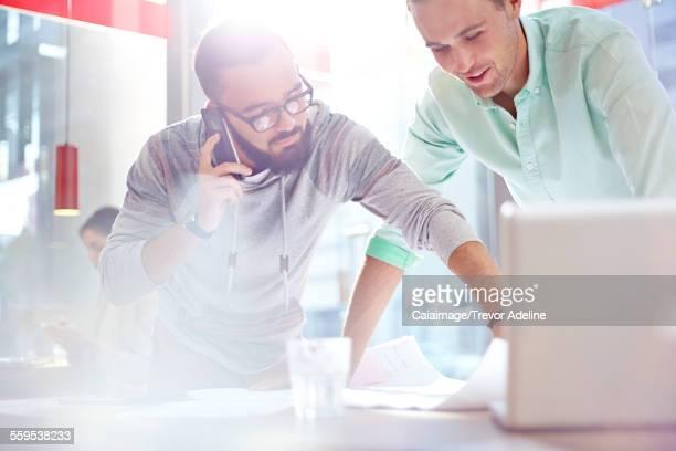 Creative businessmen reviewing blueprints
