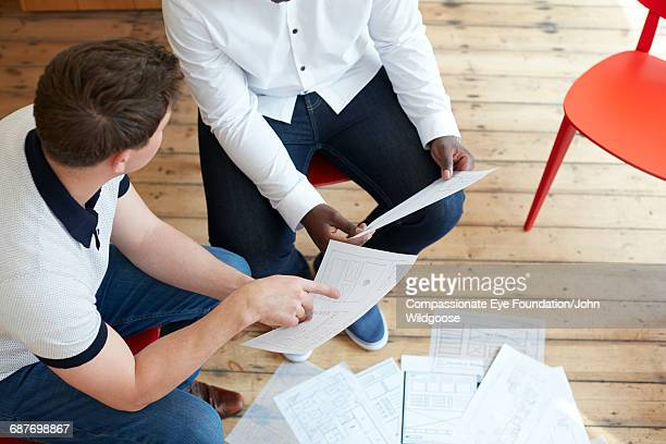 Creative businessmen reviewing proofs in office