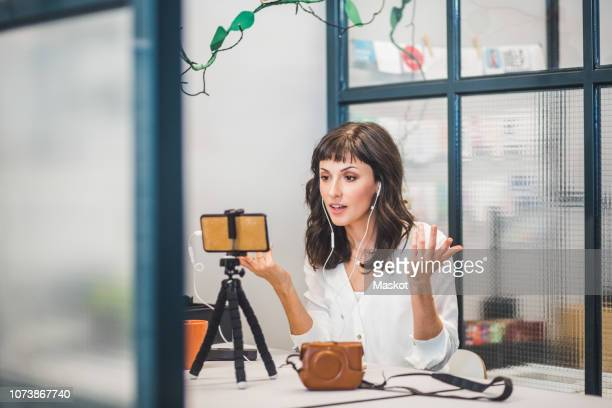 creative businesswoman attending video conference through mobile phone at desk in office - vlogging stock pictures, royalty-free photos & images