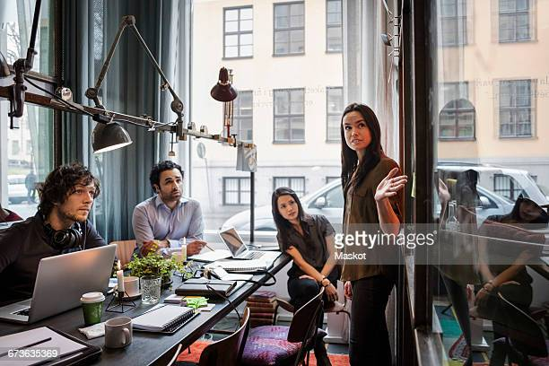 Creative businesswoman giving presentation to colleagues in modern office