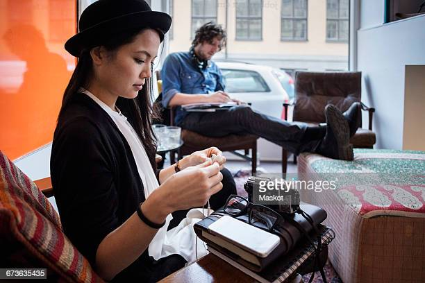 Creative businesswoman holding headphones with colleague working in background at office