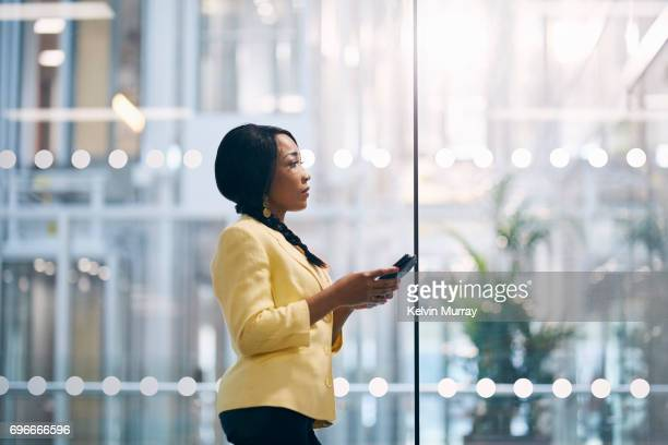 creative businesswoman texting on cell phone in office - computer software stock pictures, royalty-free photos & images