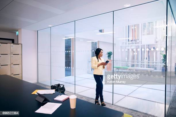 Creative businesswoman texting on mobile in conference room