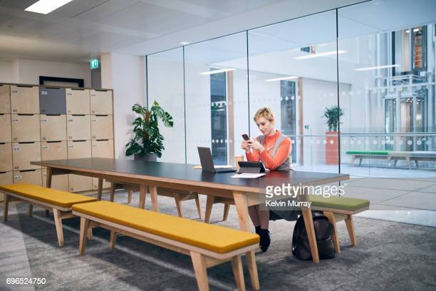 Creative Businesswoman using cell phone in conference room