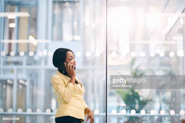 Creative businesswoman using cell phone in modern office
