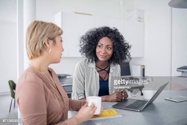 creative businesswoman with her colleague working together with laptop in the office - vanguardians stock pictures, royalty-free photos & images