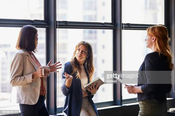 Creative businesswomen discussing by window