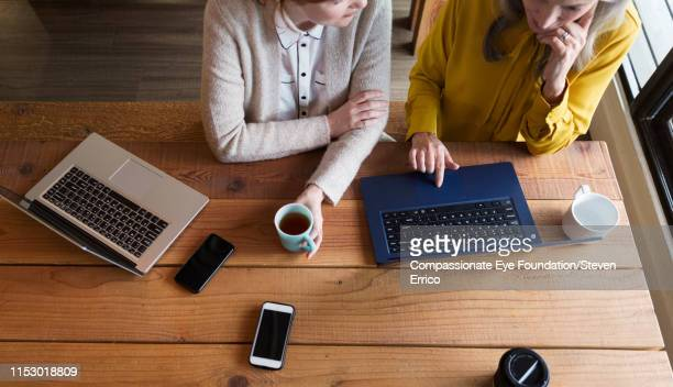 creative businesswomen having informal meeting in modern open plan office - photography stock pictures, royalty-free photos & images