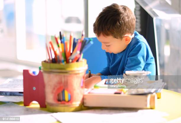 Creative child coloring on paper in playroom