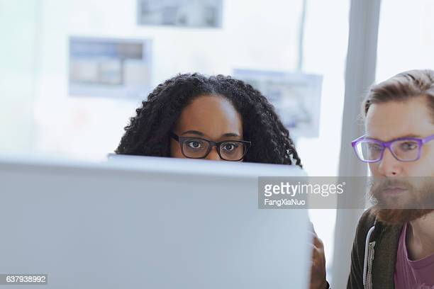 creative colleagues collaborating behind computer in office - pair stock pictures, royalty-free photos & images