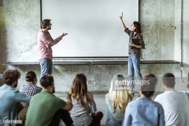 creative colleagues giving a presentation to large group of people in board room. - presenter stock pictures, royalty-free photos & images