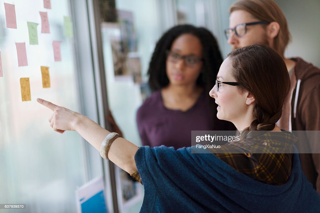 Creative colleagues reviewing ideas on wall in studio office : Stock Photo