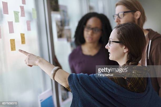 Creative colleagues reviewing ideas on wall in studio office