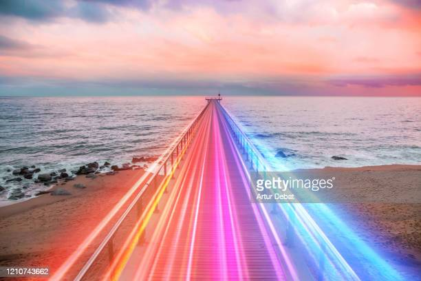creative composition of colorful lights trails in motion over the sea. - sterk perspectief stockfoto's en -beelden