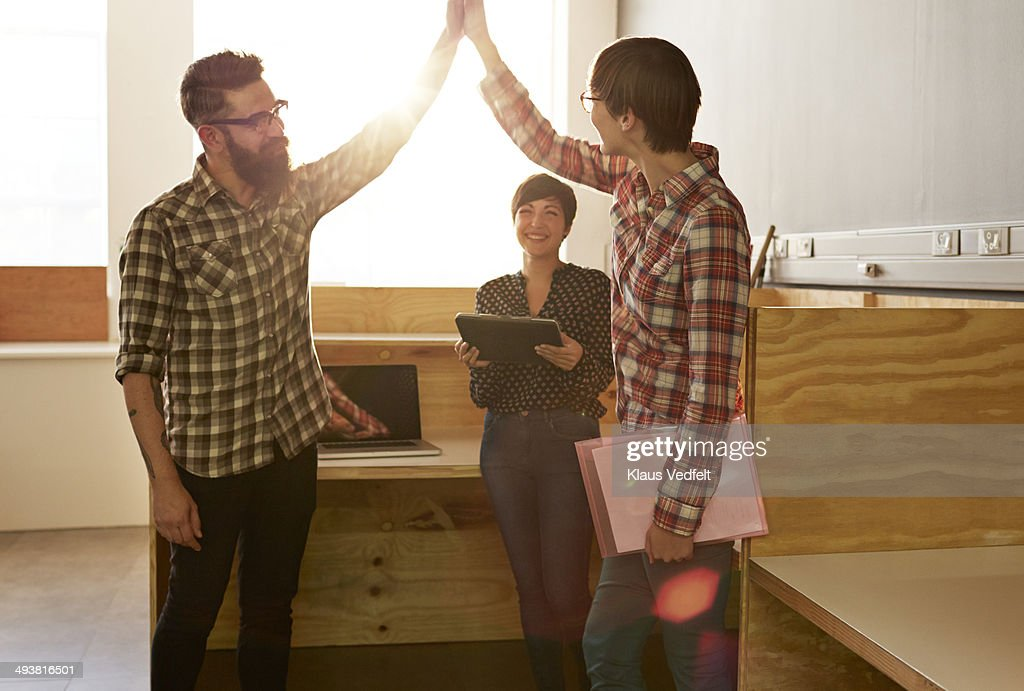 Creative coworkers doing high five at office : Stock Photo