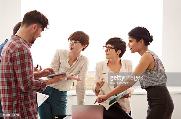 creative coworkers having stand up meeting - leanincollection stock pictures, royalty-free photos & images