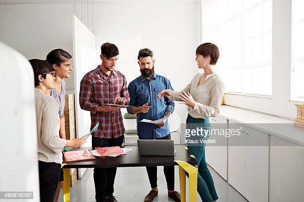 Creative coworkers in stand up meeting at office
